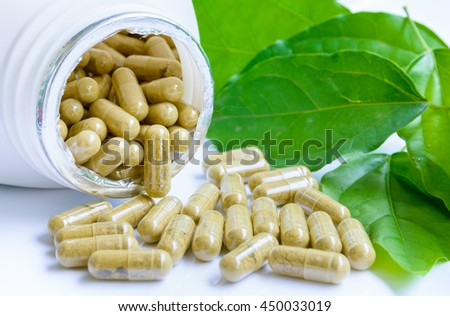 Herbal medicine capsules spilling out of a bottle,close up image. - stock photo