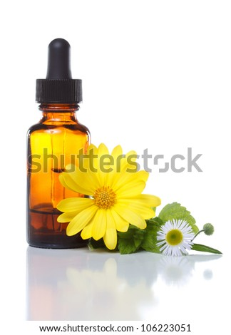 Herbal medicine dropper bottle with flowers - stock photo