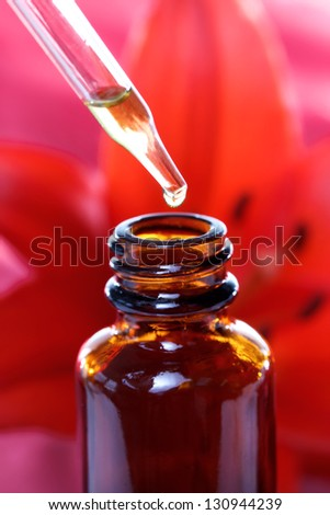 Herbal Medicine Dropper Bottle with Red Lily - stock photo