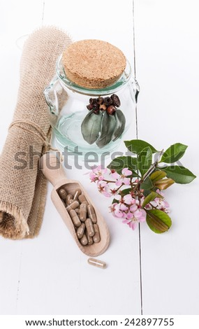 Herbal medicine pills and hawthorn flowers  over white background - stock photo