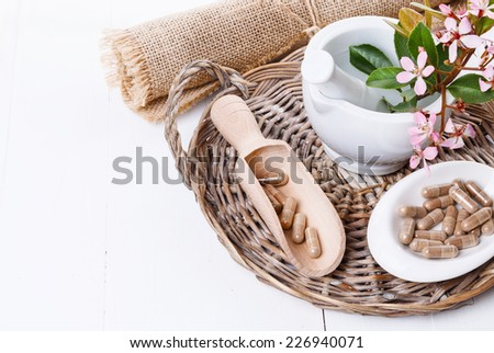 Herbal medicine pills on a woven tray and mortar over white background - stock photo
