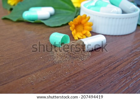Herbal medicine pills with healing herbs - stock photo