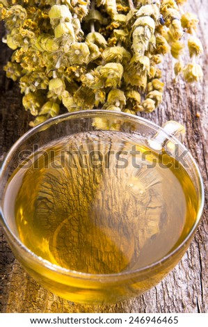 Herbal medicine series: Sideritis taurica herbal tea and flowers on wooden background - stock photo