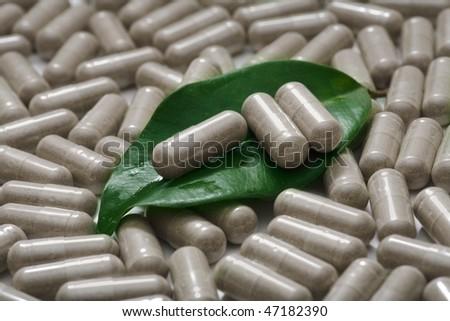 herbal medicine - three pills on green leaf over film of pills - stock photo