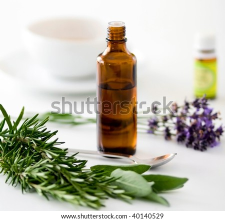 Herbal medicine with herbs and a cup of tea on table. Isolated white background. Studio shot. - stock photo