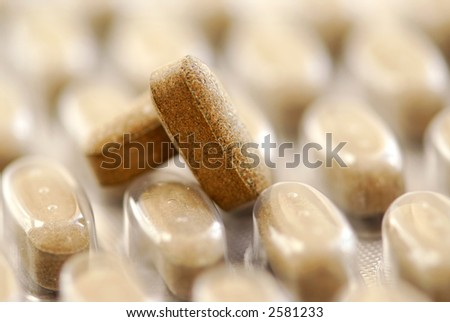 Herbal pills and package of herbal supplement close up - stock photo