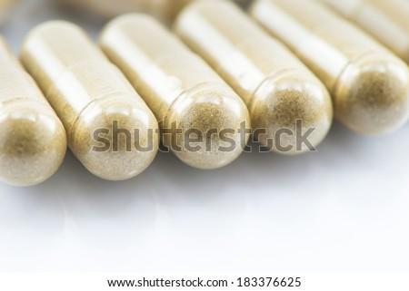 Herbal powder capsules on white glass background - stock photo