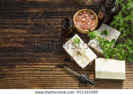 Herbal spa therapy with body oil, natural soap, salt and green herb - stock photo