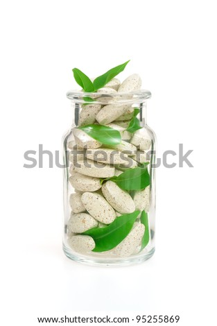 Herbal supplement pills and fresh leaves  in glass - alternative medicine concept - stock photo