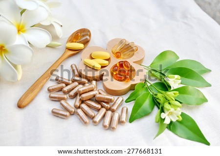 Herbal supplements and vitamins  on wooden tray and wooden spoon, decorated with white flowers and green leafs background as white cotton cloth  - stock photo