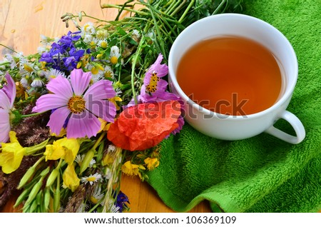 Herbal tea and flowers composition - stock photo