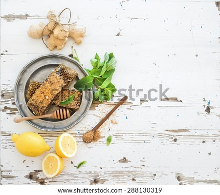 Herbal tea cooking set. Fresh mint, honeycombs, lemon, ginger on rustic white wooden background. Top view, copy space - stock photo