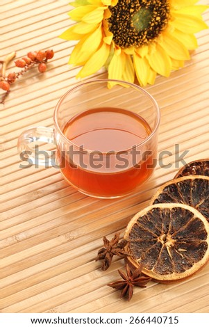 Herbal Tea Cup and Dried Lemon with Sunflower on Wooden Background - stock photo