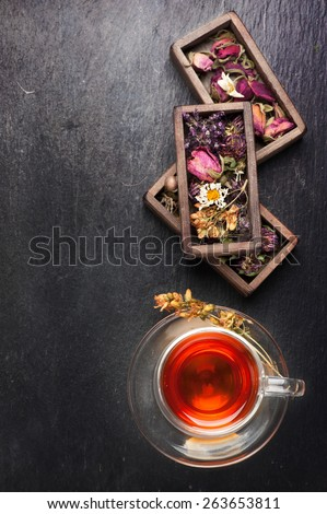Herbal tea, dried herbs and flowers on black stone background - stock photo
