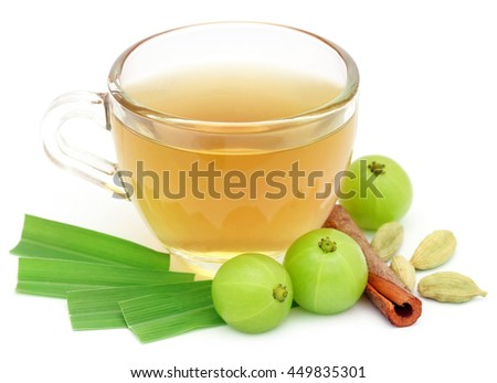 Herbal tea in a cup with different herbs over white background - stock photo