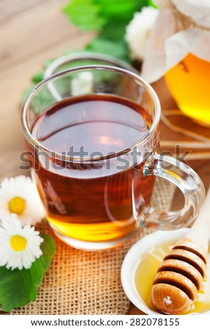 Herbal tea in a glass bowl with chamomile flowers and honey on rustic wooden background, selective focus