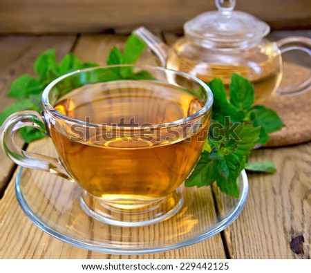 Herbal tea in a glass cup and teapot, fresh leaves of mint on a wooden boards background - stock photo