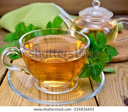 Herbal tea in a glass cup and teapot, fresh mint leaves, a napkin on a wooden boards background - stock photo
