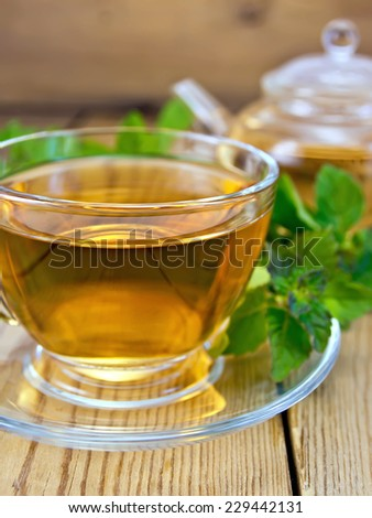 Herbal tea in a glass cup and teapot from mint, fresh mint leaves on wooden board - stock photo