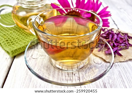 Herbal tea in a glass cup, teapot, fresh and dried flowers of Echinacea, napkin on a wooden boards background - stock photo