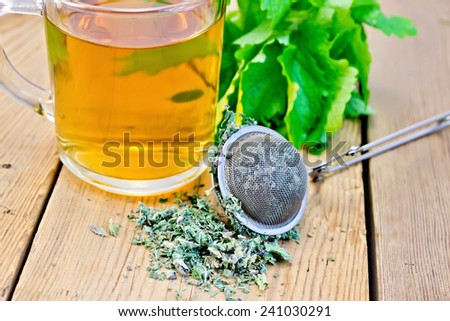 Herbal tea in a glass mug, metal sieve with dry mint leaves, fresh mint leaves on a wooden boards background - stock photo