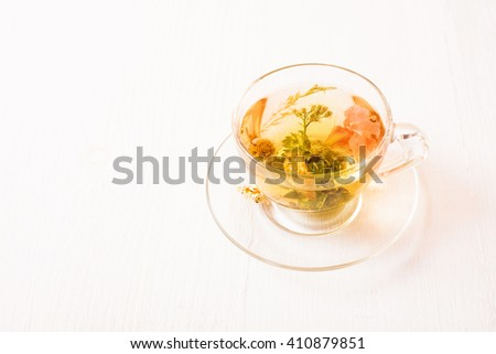 Herbal tea in a transparent cup on white table - stock photo