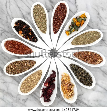 Herbal tea selection in white porcelain dishes over marble background. - stock photo