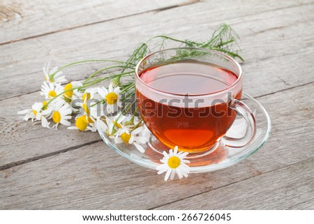 Herbal tea with chamomile flowers on wooden table background - stock photo