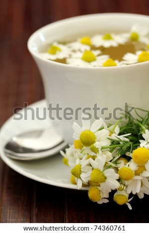 herbal tea with chamomile on a wooden table, shallow dof - stock photo