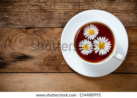 herbal tea with chamomile on old wooden table. Top view. With place for text. - stock photo