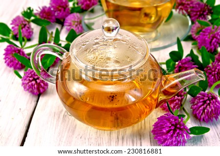 Herbal tea with clover flowers in a glass cup and teapot on background light wooden boards - stock photo