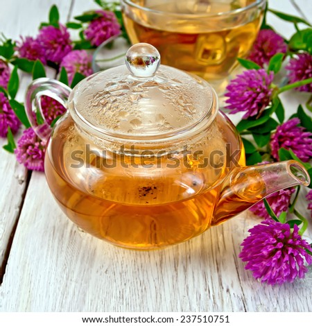 Herbal tea with clover flowers in a glass teapot and cup on the background light wooden boards - stock photo