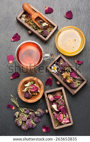 Herbal tea with honey, dried herbs and flowers on black stone background - stock photo