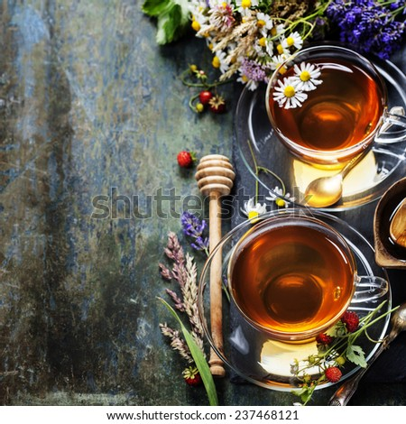 Herbal tea with honey, wild berry and flowers on wooden background  - stock photo