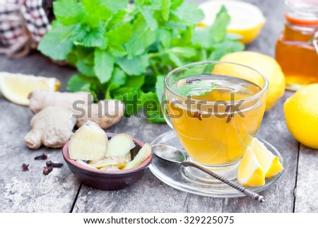 Herbal tea with lemon and ginger on wooden table - stock photo