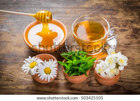 Herbal tea with mint, chamomile, jasmine flowers and honey on old rustic table