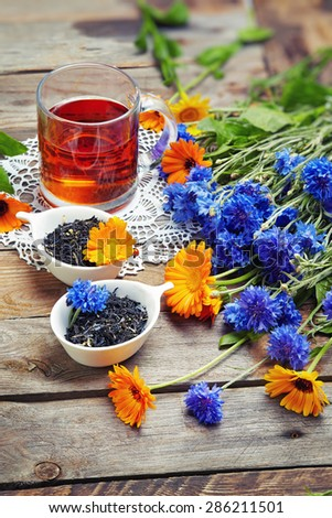 Herbal tea with wild flowers(calendula, blue cornflower) on wooden background  - stock photo
