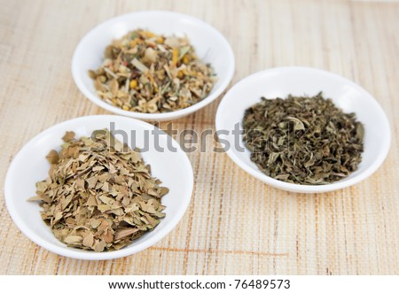 Herbal teas in small white bowls on natural matting, focus on front left tea. - stock photo