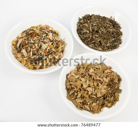 Herbal teas in small white bowls on white background. - stock photo