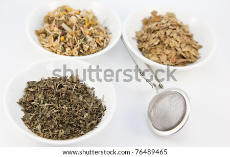 Herbal teas in small white bowls with cup infuser, focus on front left tea and infuser. - stock photo