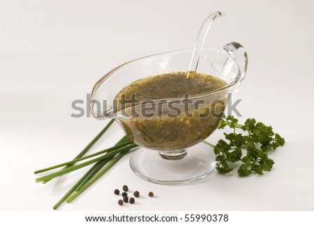 Herbal vinaigrette dressing in a glass sauce-boat. - stock photo