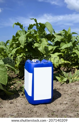 Herbicide container in the field of tobacco - stock photo