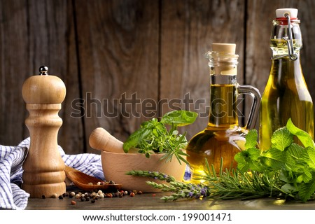 herbs and oil on wooden table - stock photo