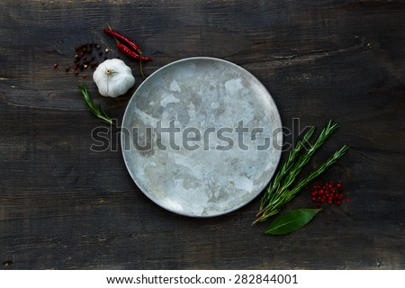 Herbs and spices around old plate on dark wooden background, top view, place for text - stock photo