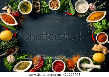 Herbs and spices over black stone background. Top view with copy space - stock photo