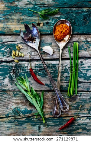 Herbs and spices selection - old metal spoons and rustic wooden background - cooking, healthy eating. Top view. - stock photo