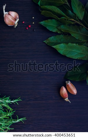 Herbs and spices selection - rosemary, garlic, Bay leaf and pepper on dark wooden background. Background layout with free text space. Copy space. Top view. Food flat lay. - stock photo