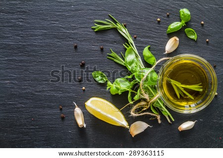 Herbs background - rosemary, basil, mint, lemon, olive oil, garlic, pepper, dark stone background, top view - stock photo