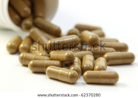 Herbs capsules spilling out of a bottle. Isolated on white background. - stock photo