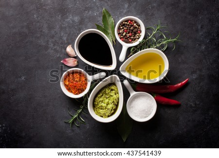 Herbs, condiments and spices on stone background. Top view
